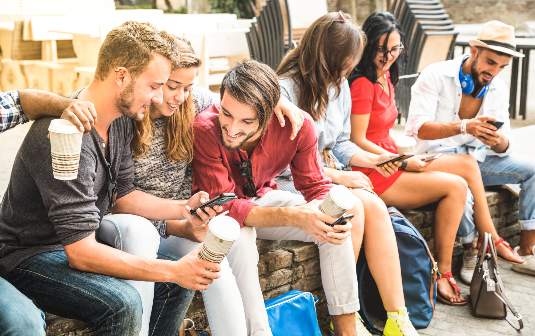 Multiracial millennials group using smart phone at city college backyard – Young people addicted by mobile smartphone – Technology concept with connected trendy friends – Warm vibrance sunshine filter