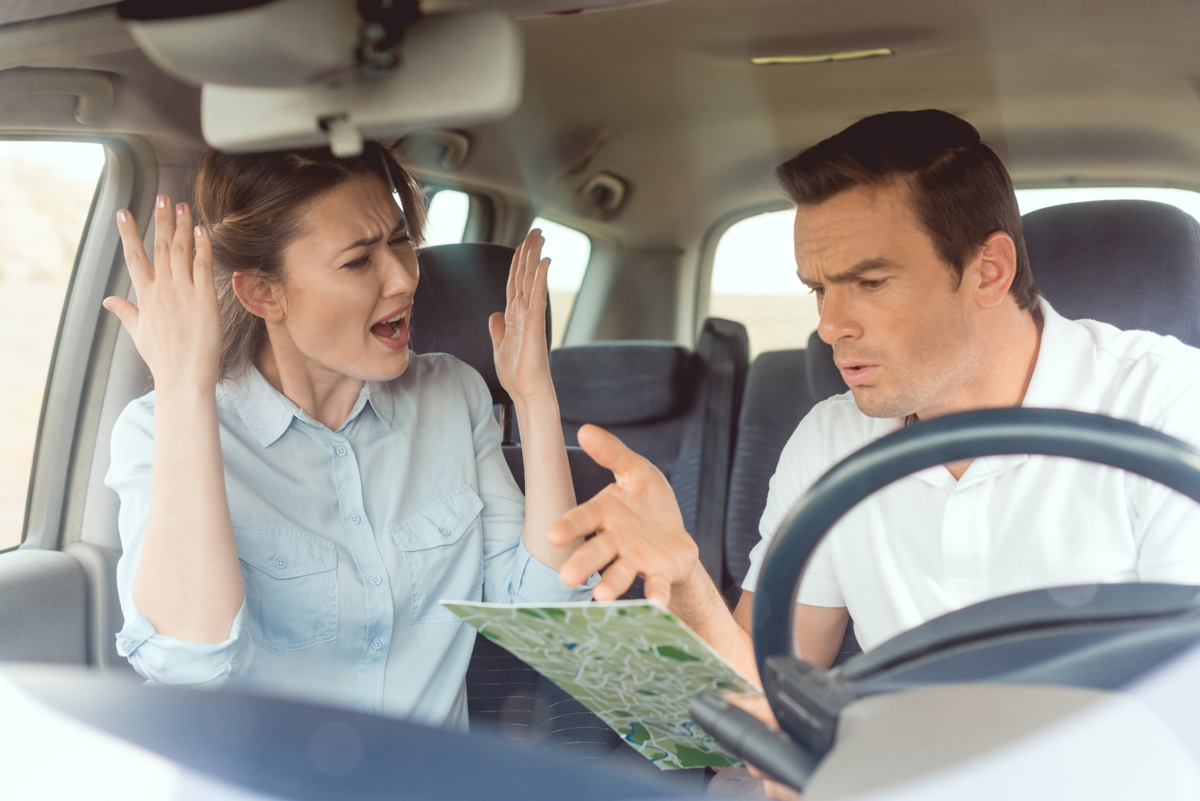 adult couple having quarrel while travelling by car